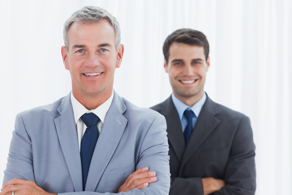 Smiling businessmen posing in bright office looking at camera